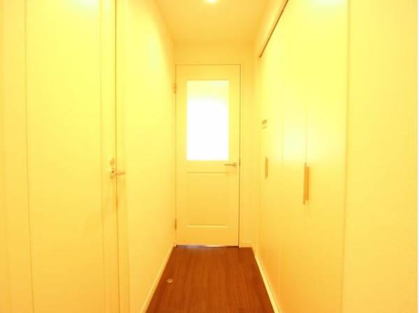 玄関を開けると、明るい日が差し込むリビングへと誘う廊下。毎日の行き帰りで使う大事な玄関は、落ち着きのある空間に。
