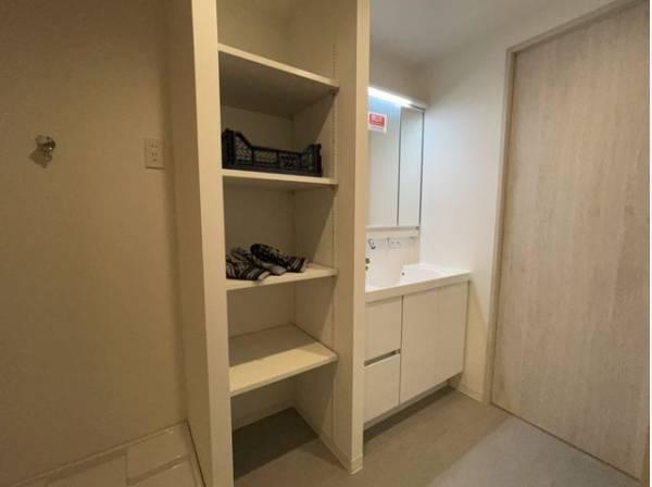 洗面化粧台の横には収納棚を設置。一日の始まりと終わりを心地よく演出してくれる場所です。