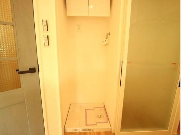 洗濯機置場はキッチンにあります。生活感が出ないよう、洗濯機を扉の中へ収納し、普段は見えないようにしました。