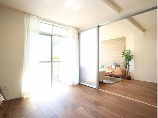 リビングと隣接の洋室は天井、フローリングと同じ色合いで揃えており、可動ドアを開くと広々とした空間に。家族構成の変化にも柔軟に対応するための工夫をいたしました。