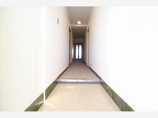 玄関を開けると、明るい日が差し込むリビングへと誘う廊下。広々開放的な空間。