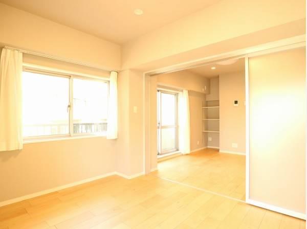 隣接するリビングとの色味を合わせながら、落ち着きのあるシンプルなお部屋に仕上げました。引戸を開けると開放感のある空間に。