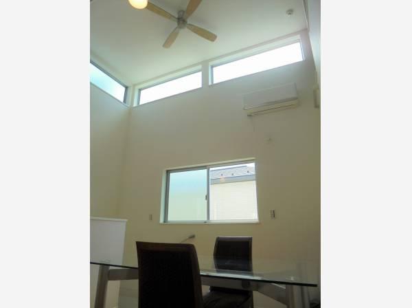 吹抜けの天井から陽が差し込む、明るい居住空間。