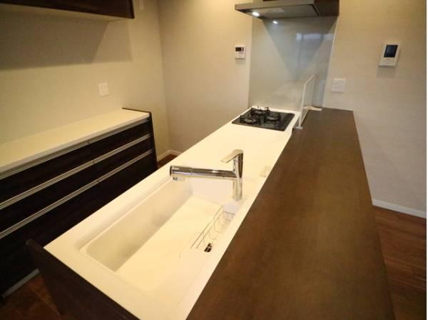 白のワークトップが目を引くスタイリッシュなキッチン。背面にはカウンター収納を設けています。